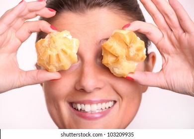 A close up of a young woman covering her eyes with cream puffs over white background