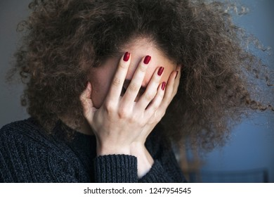 Close up of young woman with depression and bulimia sitting alone in gray room. She covers her face with hands. Mental problems with depression and bulimia.