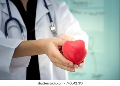 Close up of young woman doctor holding a red heart,Health concept