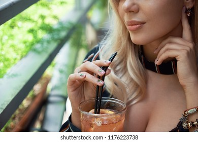 Close up young woman drinking tasty sweet, fresh lemonade, holding straws with fingers, beautiful manicure design, touching cheek with a hand, amazing relaxing day. Appealing decolletage, full lips.
