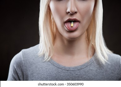 Close up of young woman drugging herself. The woman is standing and holding a pill on her tongue