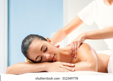 Close up of young woman enjoying relaxing body massage. Therapist doing manipulative treatment on shoulders.