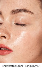 close up of young woman with eyes closed, coral lips and wet skin