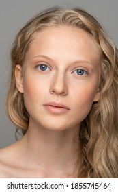 Close up of young woman face with blue eyes, curly natural blonde hair and eyebrows, has no makeup, looking at camera. Girl with perfect fresh clean skin over studio grey background. Youth concept.