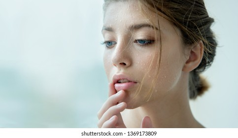 Close up of young woman face  with clean perfect skin and water moisture drops  touching face. Macro portrait of beauty model with natural nude makeup moisturizing her skin. Spa, skincare.
