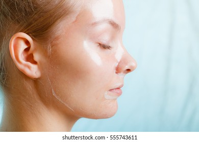 Close up young woman in facial peel off mask. Peeling. Beauty and skin care. Side view