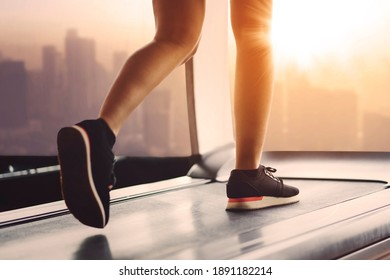 Close up of young woman foot running on the treadmill while exercising in the fitness center with sunset background