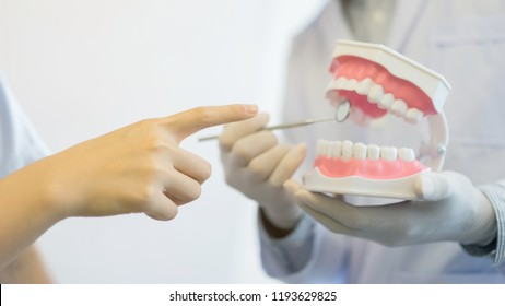 close up young woman hand point on teeth model denture and dentist use explorer mirror tool for advice and explaining to patient at clinic office , health care concept