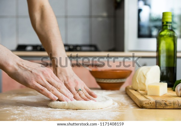 Close up of young woman hands kneading a dough on a wooden board. She is standing in the kitchen, behind a table, next to a window decorated with christmas lights