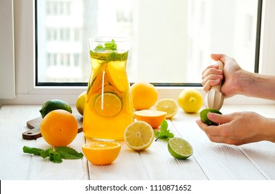 Close up of young woman hands making fresh lemonade, squeezing juice out of citrus fruits, juicer. Pitcher full of cold beverage with lemon, orange, lime & mint leaves. Window background, copy space.