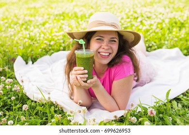 Close up of Young woman have fun in the park and drink green smoothies at a picnic.