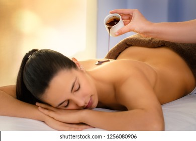 Close up of young woman having antioxidant chocolate cosmetic treatment in spa.Therapist pouring hot cacao massage oil on girl's back. Low light relaxed  atmosphere.