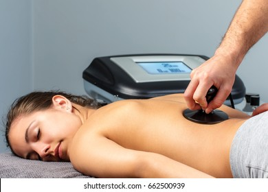 Close up of young woman having electrotherapy session.Therapist stimulating nerves and muscles on female spine.