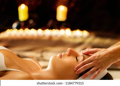 Close up of young woman having healing head massage in spa.Therapist doing manipulative treatment with essential oils on  forehead. Low key scene with candles glowing in background.