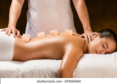 Close up of young woman having hot Himalayan stone massage in spa.Natural salt stone bricks placed on spine with therapist in background.