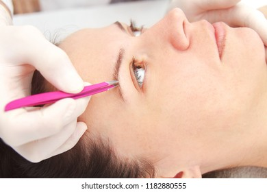 Close up of the Young woman having professional eyebrow correction procedure in beauty salon