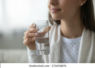 Close up of young woman hold glass with clean pure mineral water, recommend healthy lifestyle, prevent dehydration, millennial female feel thirsty, enjoy aqua for body refreshment, skincare concept