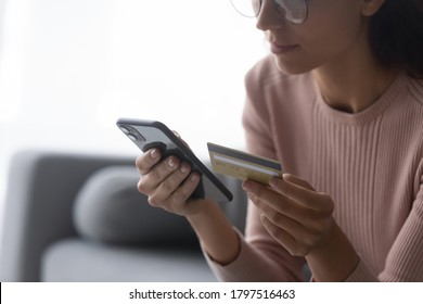 Close up of young woman hold smartphone and credit card make purchase on internet, female in glasses pay bills taxes using web banking service system on cellphone gadget, new technology concept