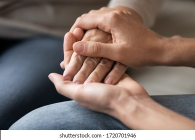 Close up young woman holding female hand of older mother, caring adult grown up daughter supporting and comforting mature mum, expressing love, two generations trusted relations