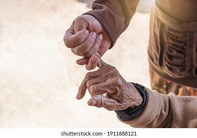 Close up of young woman holding hand of her mother, family time, hook each other's little finger. Selective focus on young woman hand holding senior woman and young adult woman caring for the elderly.