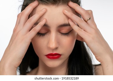 Close up of a young woman holding her head with a headache.