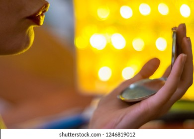 Close up of a young woman holding a mirror and puckering her lips with yellow lights in the background