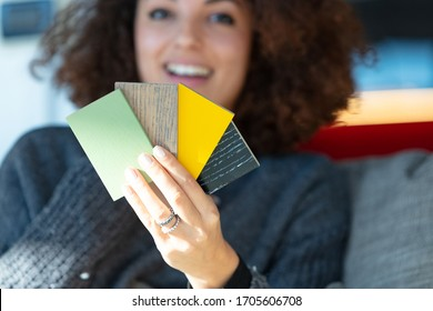 A close up of a young woman holding multiple paint colour or cladding samples.