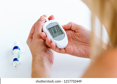 Close up of young woman looking the results of glucose test on the glucometer over white background.