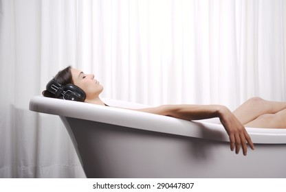 Close up of young woman lying in a bathtub listening to music with big headphones on her head. Concept of relaxation and freedom.