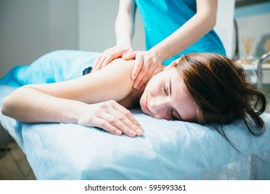Close up young woman lying vestured turquoise towel while massage therapist massaging her shoulders. Beauty, health life and cosmetology concept.