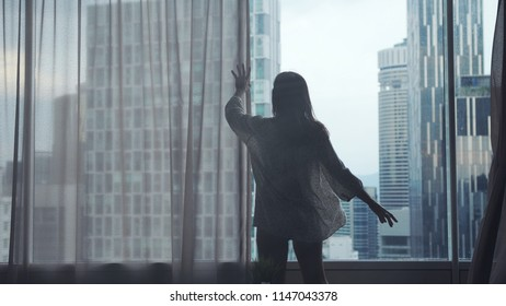 Close up of young woman opening window curtains