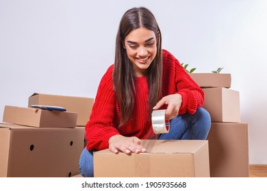 Close up of Young woman packing cardboard box. Moving house concept. Beautiful girl taping up a cardboard box with adhesive tape.