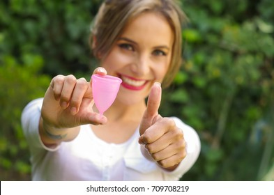 Close up of a young woman pointing in front of her a menstrual cup in one hand, Gynecology concept, ith her thums up aproving the use of the mentrual cup, in a blurred background