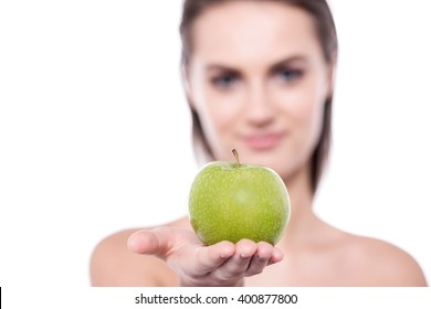 Close up of young woman posing to camera with an apple in her hand