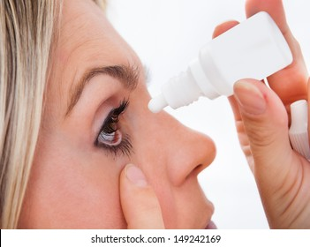 Close up young woman pouring drops in her eyes on white background