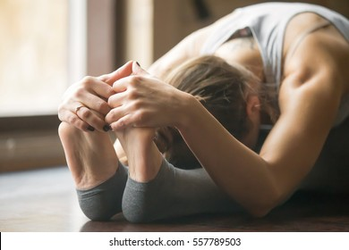 Close up of young woman practicing yoga, sitting in Seated forward bend exercise, paschimottanasana pose, working out, wearing sportswear, grey pants, bra, indoor, home interior background, horizontal