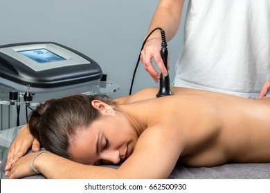 Close up of young woman receiving interferential electrotherapy.Therapist stimulating nerve on spine with apparatus.