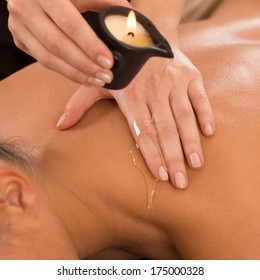 Close Up Of A Young Woman Receiving Shoulder Candle Massage At Spa