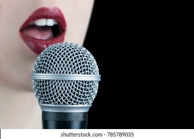 Close up of a young woman with red lips singing to the microphone isolated on black background