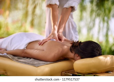 Close up of young woman is relaxing in spa and wellness center while receiving massage in nature