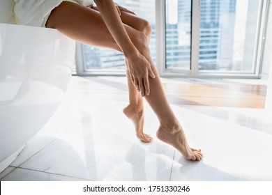 Close up young woman sitting on bath in modern bathroom with windows, touching legs, enjoying perfect smooth silky skin after epilation or home depilation procedure, applying moisturizing body cream