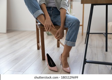 Close up young woman sitting on chair, taking off high heel shoes, massaging tired foot relieving pain ache in office. Exhausted millennial lady feeling feet discomfort, wearing narrow footwear.