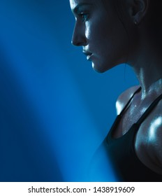 Close up of young woman in sports bra with sweat against blue background. Muscular build female relaxed after workout.