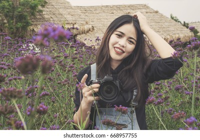 Close up young woman taking photo in a Flowers field