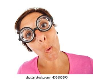 Close up of a young woman with  thick glasses and surprised expression on white background