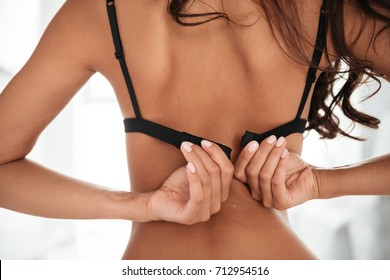 Close up of a young woman in underwear sitting and buttoning up her bra indoors