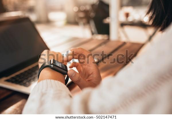 Nahaufnahme junger Frauen mit intelligenter Armbanduhr in einem Café. Weibliche saß an einem Tisch und überprüfte ihre intelligente Uhr.