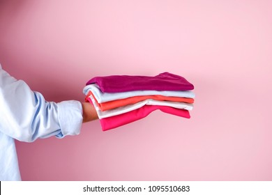 Close up of young woman wearing blue cotton shirt holding stack of perfectly folded multicolor shirts. Female w/ pile of different color clothing in her hands on pale pink background. Laundry concept.