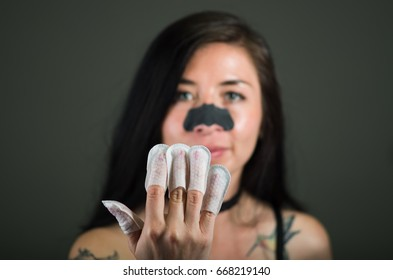 Close up of young woman wearing nails protector in her nails and a nose mask to clean skin from black spots, in a black background
