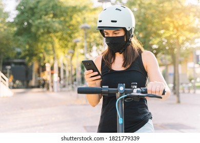 close up of a young woman wearing protective mask against coronavirus in an electric scooter using her smartphone with blurred background in a city